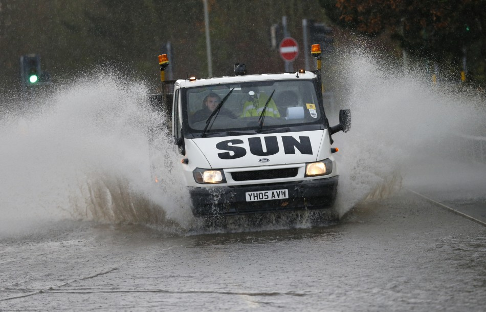 A van drives through a flooded street in Tewkesbury, south western England (Reuters)