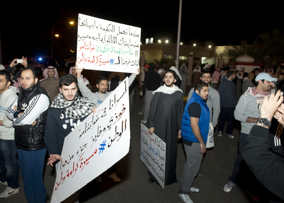 Demonstrators carry placards during a protest in Kuwait City