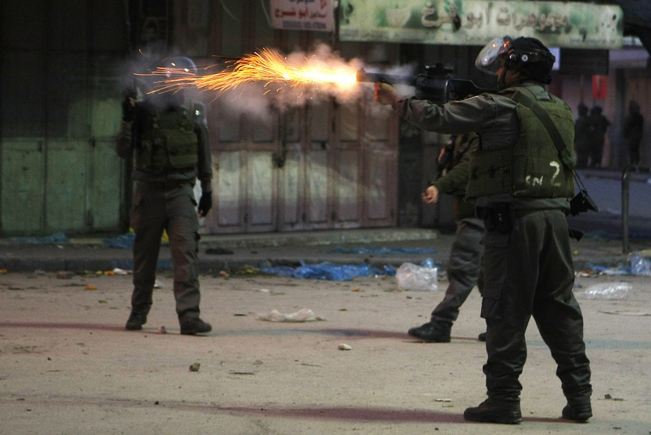 An Israeli security officer fires a tear gas