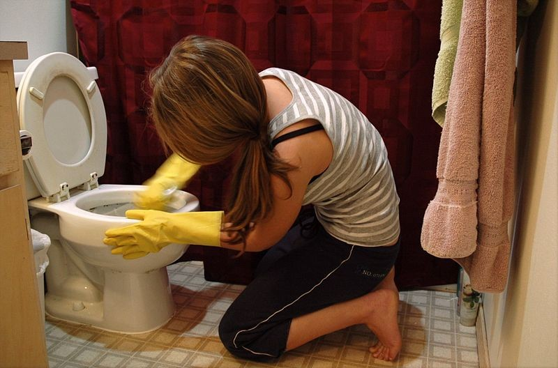 Woman cleaning toilet