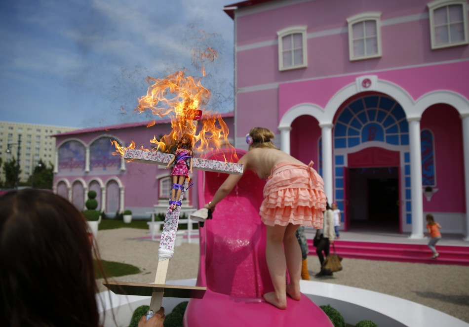 Protester burns barbie on cross in dream house protest photos