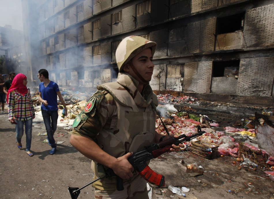An Egyptian soldier and a couple move near a burnt annex building of Rabaa Adawiya mosque. (Photo: Reuters)