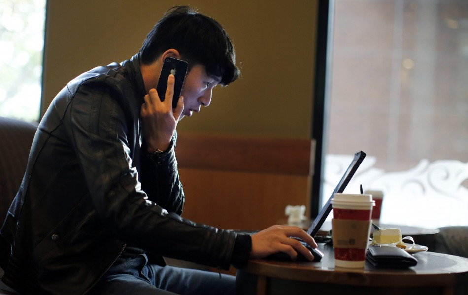 "A man talks on the phone as he surfs the internet on his laptop at a local coffee shop in downtown Shanghai November 28, 2013. China's campaign against online rumours, which critics say is crushing free speech, has been highly successful in ""cleaning"