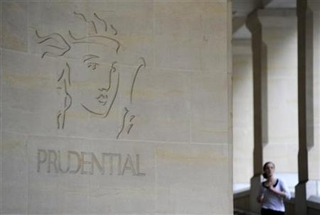A woman passes the Prudential offices in central London