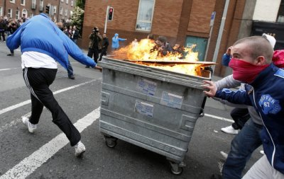 Youths push a burning rubbish bin towards riot police during disturbances at the start of the Queen039s visit to Ireland.