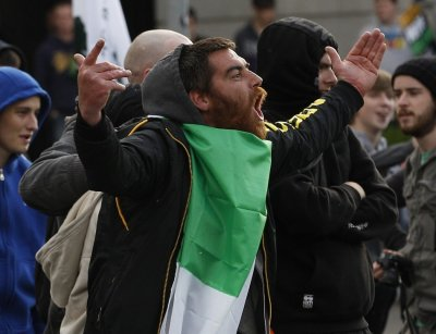 A man taunts Irish police officers during a protest over the visit by the Queen in Dublin.