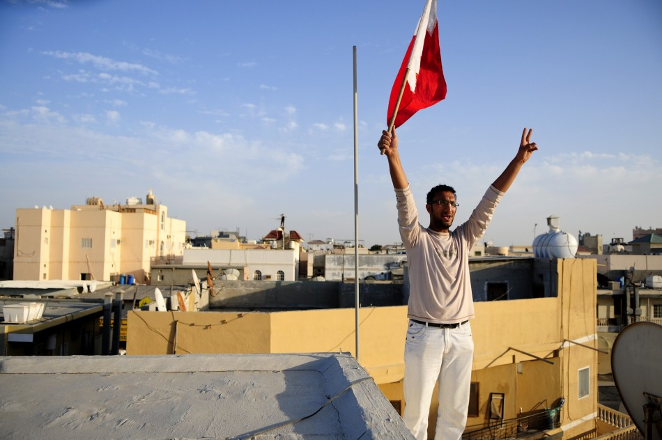 A man holds a flag as he protests against the crackdowns from a rooftop in the village of Sanabis