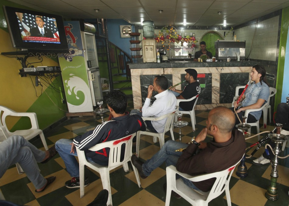 Libyans watch a television broadcast of a speech by U.S. President Barack Obama in U.S., at a shop in Benghazi