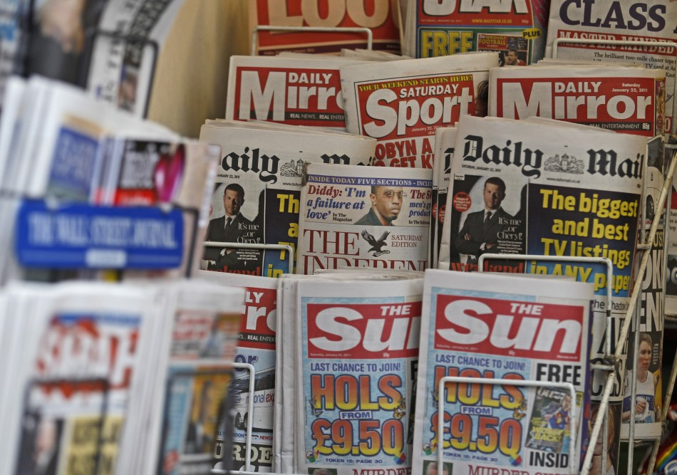British newspapers are displayed at a newsagent's stand in central London