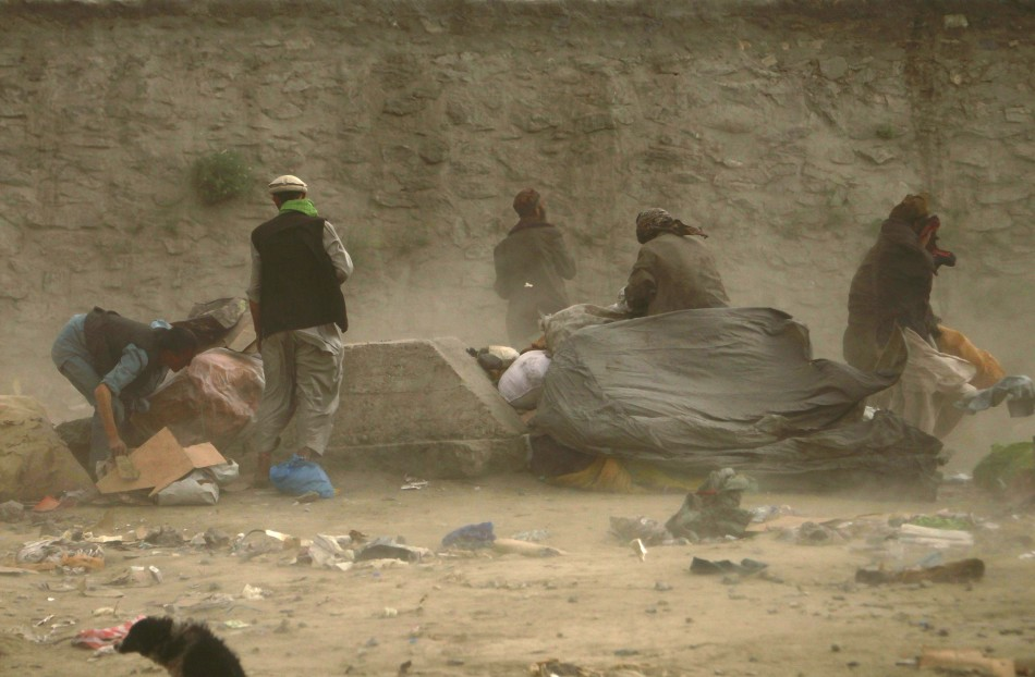 Afghan men take cover during a dusty day in Kabul