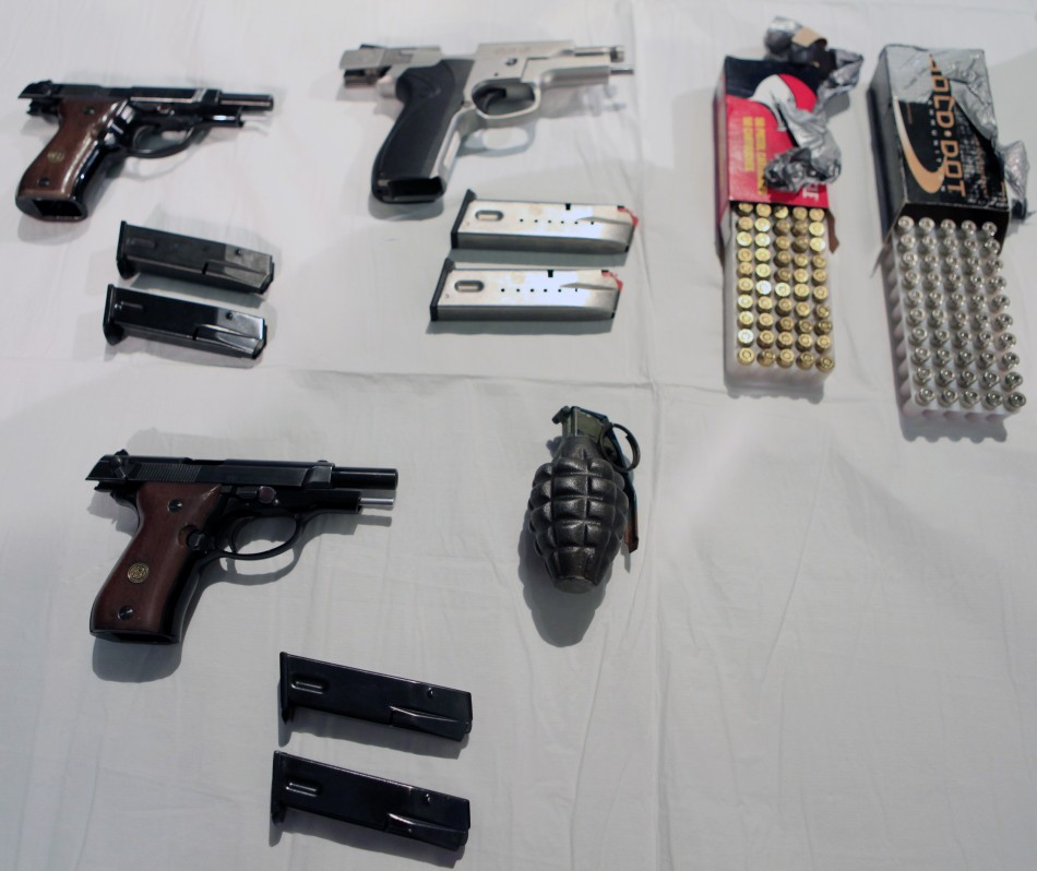 A group of weapons, ammunition and a hand grenade are displayed at a news conference at City Hall in New York
