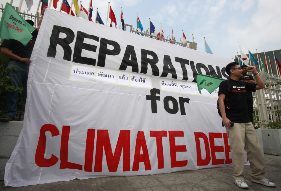 Activists from JSAPMDD shout slogan near a banner during a demonstration in front of the United Nations building in