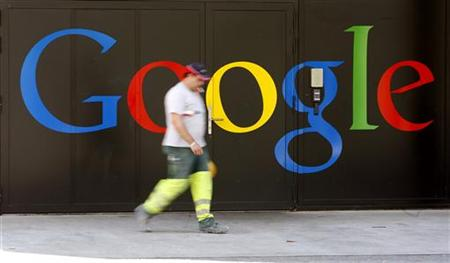 A construction worker walks past a logo next to the main entrance of the Google building