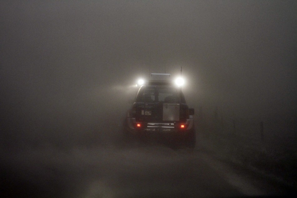 A car is seen through a cloud of ash at the Geirland farm near Kirkjubaejarklaustur.