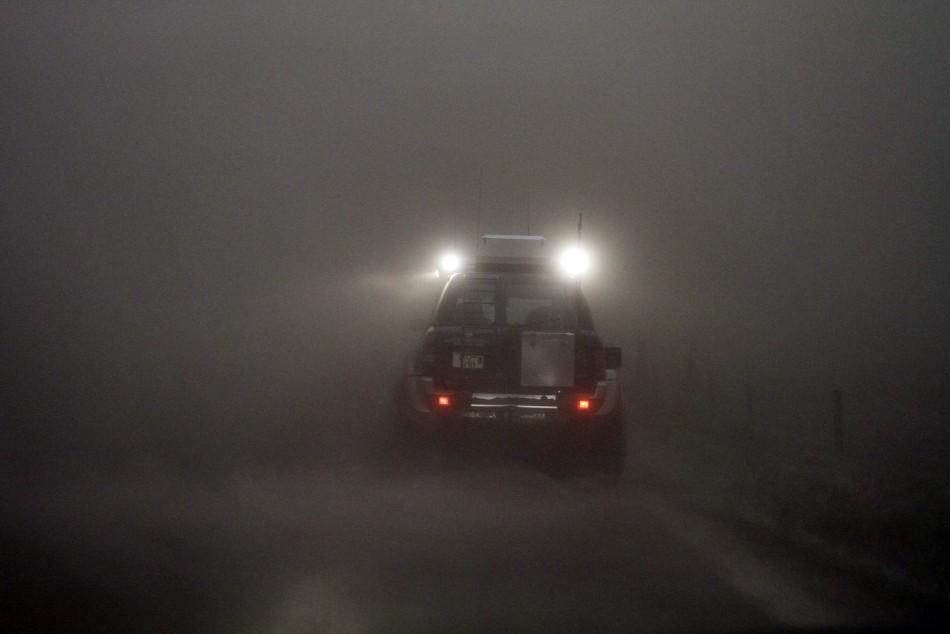 A car is seen through a cloud of ash at the Geirland farm near Kirkjubaejarklaustur.