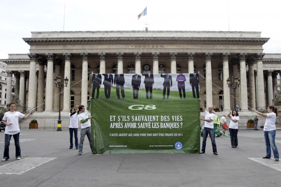 Members of the French doctors group Medecins du Monde hold a banner in front of the former Paris Bourse during an anti-G8 summit protest in Paris