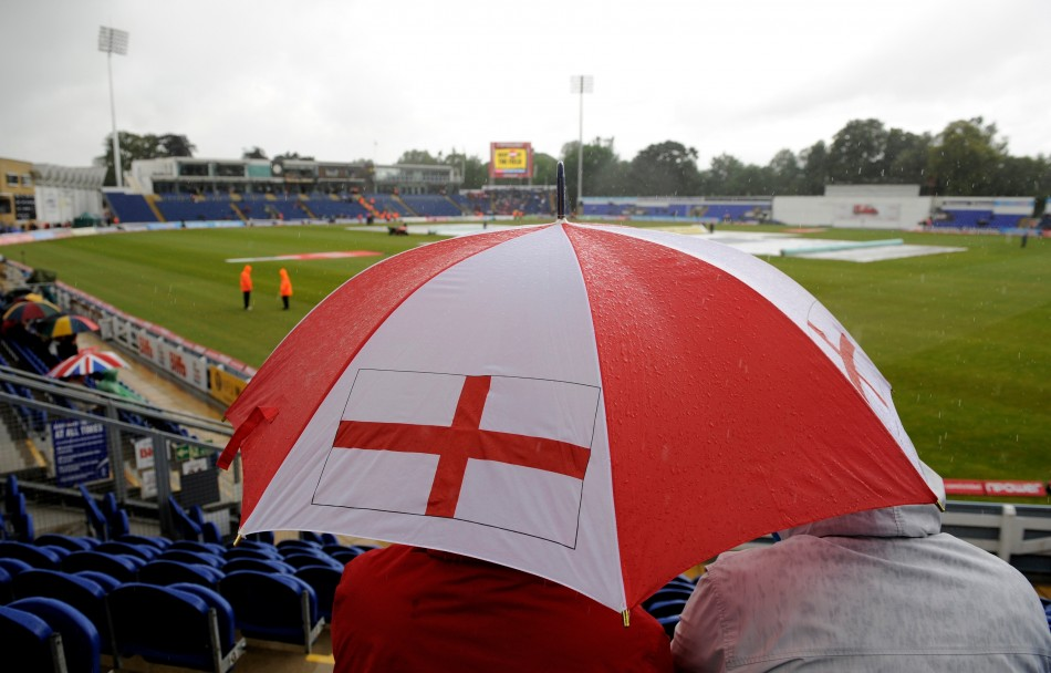 A fan waits under an umbrella as the start of the first cricket test match between England and Sri Lanka is delayed by rain at the Swalec Stadium at Cardiff.