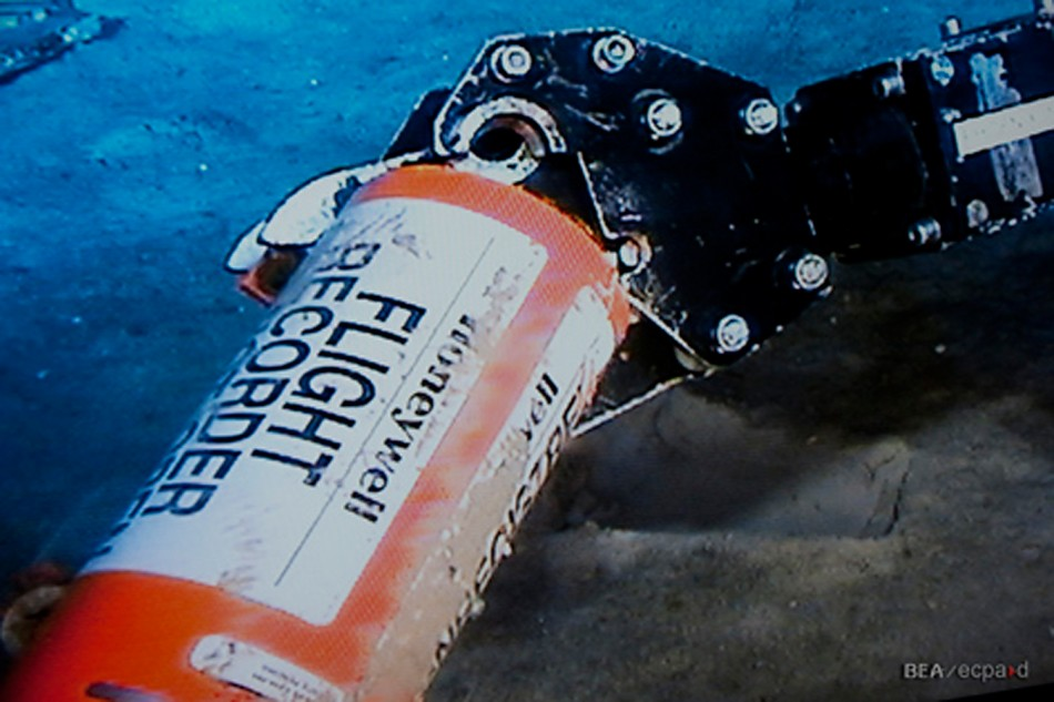 A mechanical arm, seen in this image published on the web site of France's BEA air accident inquiry office May 1, 2011, show the orange cylindrical flight data recorder above the sand