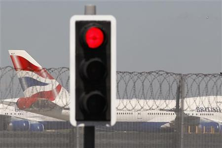 A British Airways aircraft manoeuvres behind a red traffic light at Heathrow Airport