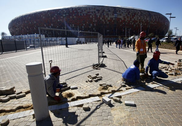 Workers pave the ground outside the Soccer City stadium in Soweto, Johannesburg