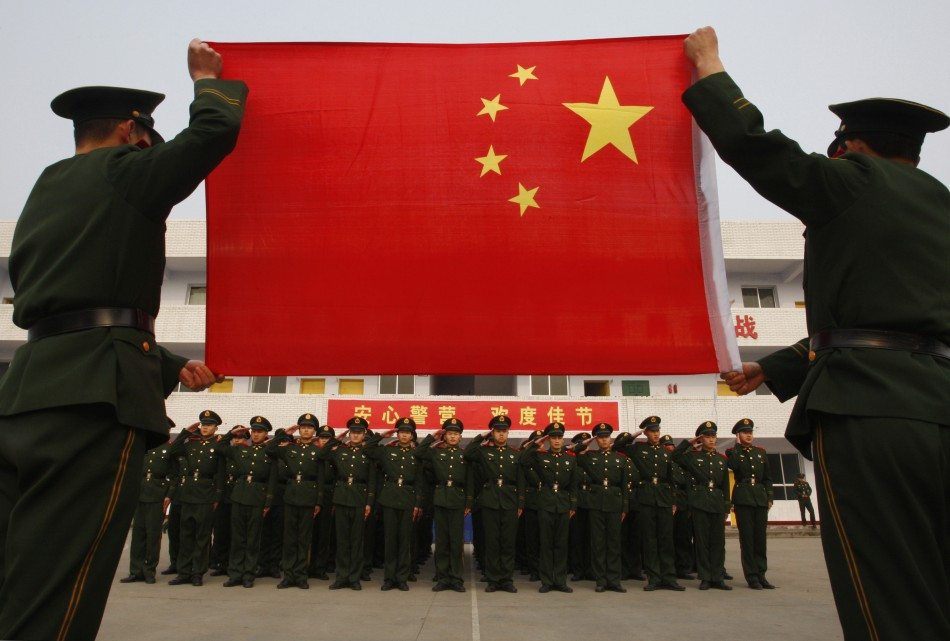 Paramilitary police recruits take an oath in front of a Chinese national flag during a military rank conferral ceremony at a military base in Suining