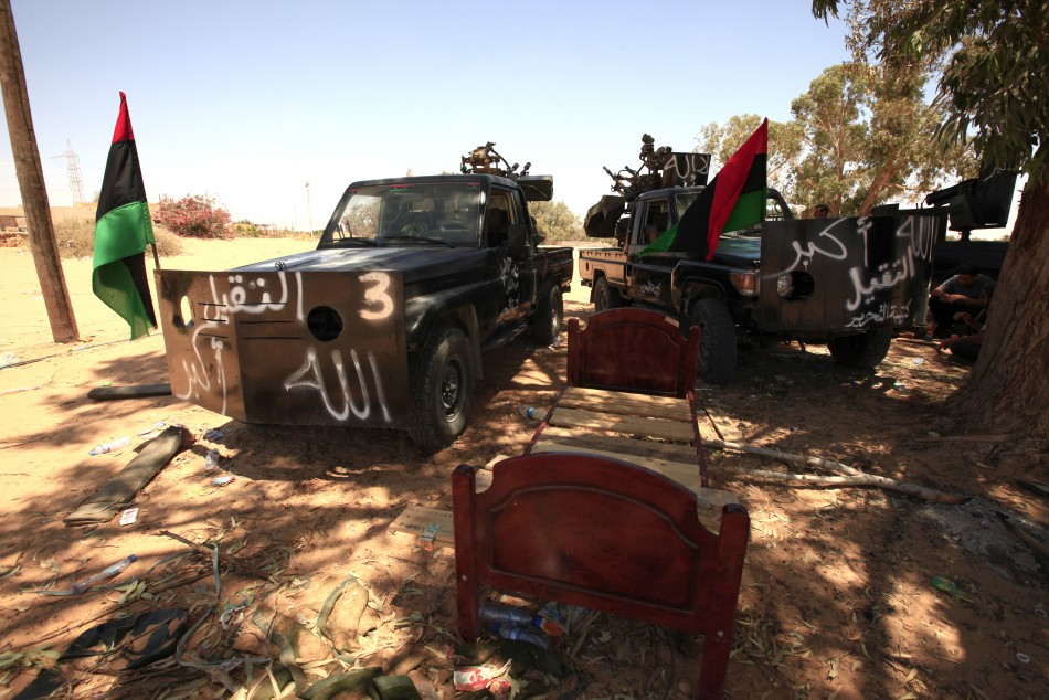 Pickups belonging to Libyan rebel fighters are seen under trees while they are on standby at Misrata's eastern front line