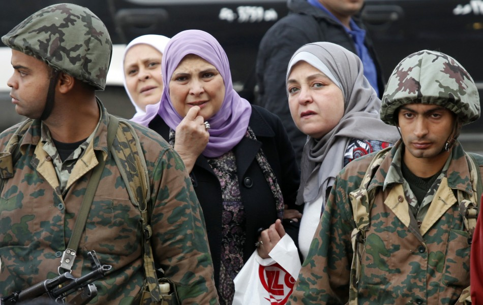 Egyptian soldiers stand in front of women at Tahrir Square in Cairo