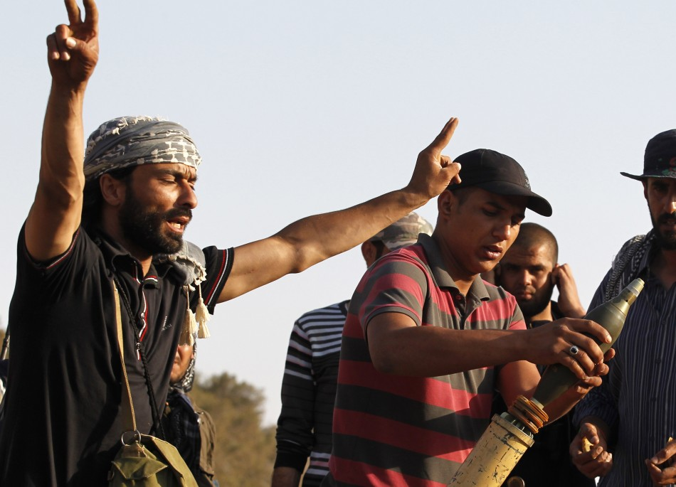 A Libyan fighter shouts while his comjrade loads a mortar at Misrata's western front line