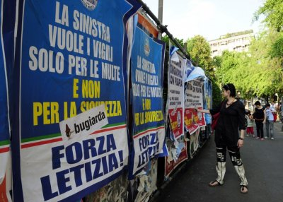 A woman looks at political banners supporting Milans mayor Letizia Moratti in downtown Milan