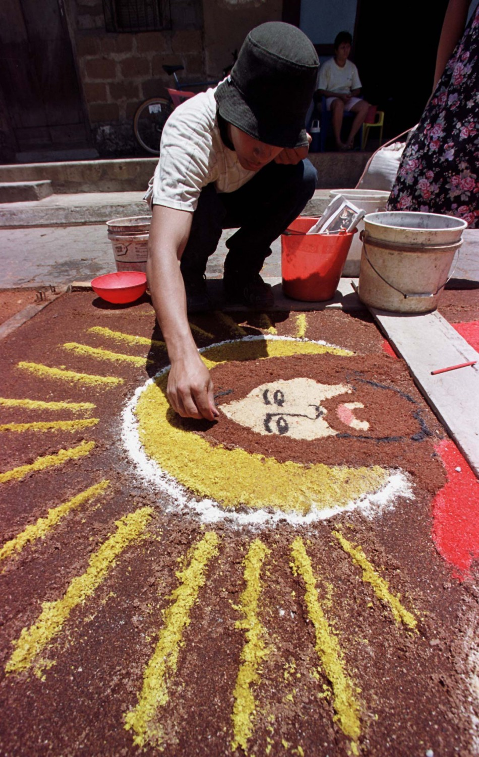 A man paints an image of Jesus Christ on a sidewalk in Leon, 90 kms west of Managua, April 21