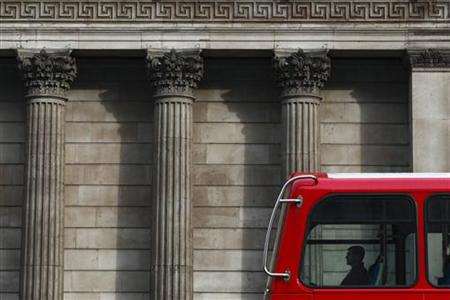A man travels in a double-decker bus as it passes the Bank of England in central London