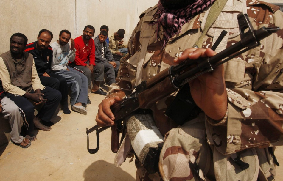 Rebel guards suspected mercenaries and forces loyal to Libyan leader Muammar Gaddafi inside a prison in Benghazi