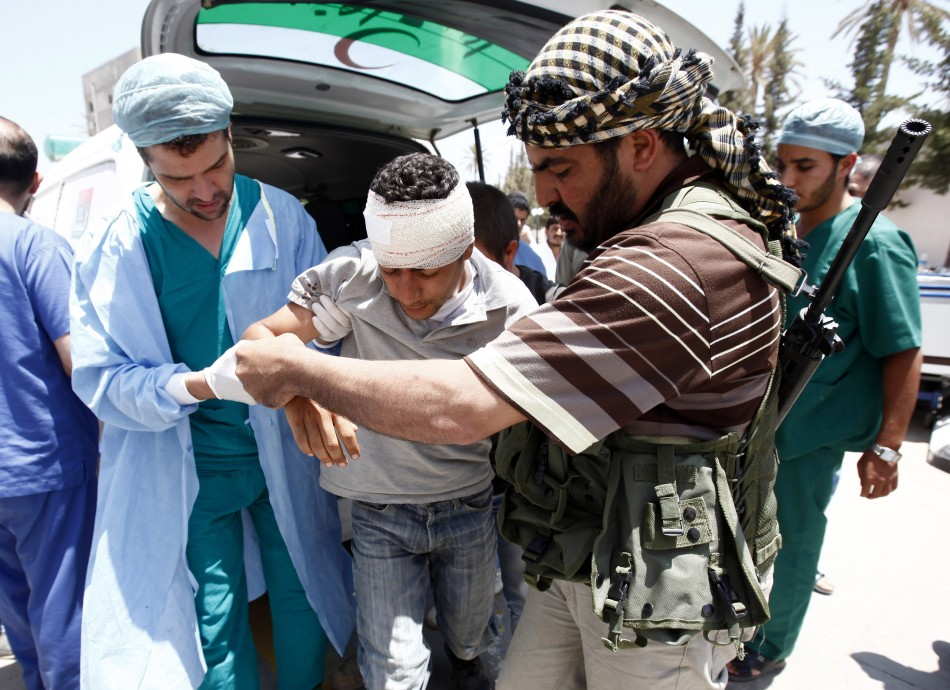 A rebel fighter and a medic assists an injured rebel fighter at a field hospital near Misrata's western front line
