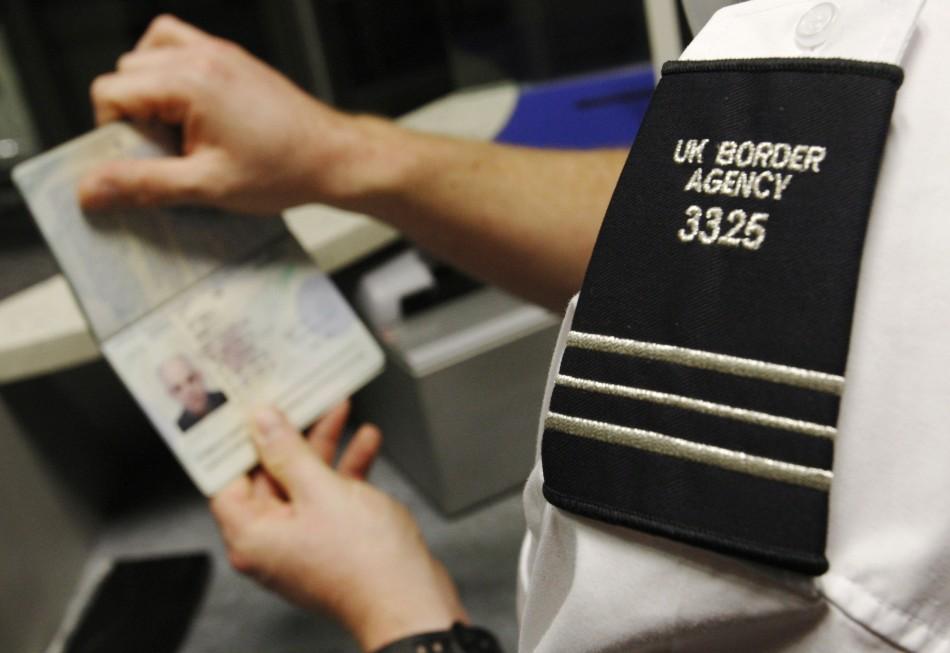 A UK Border Agency representative checks a passport
