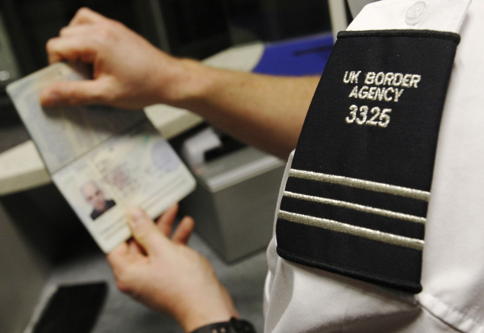 A UK Border Agency representative checks a passport
