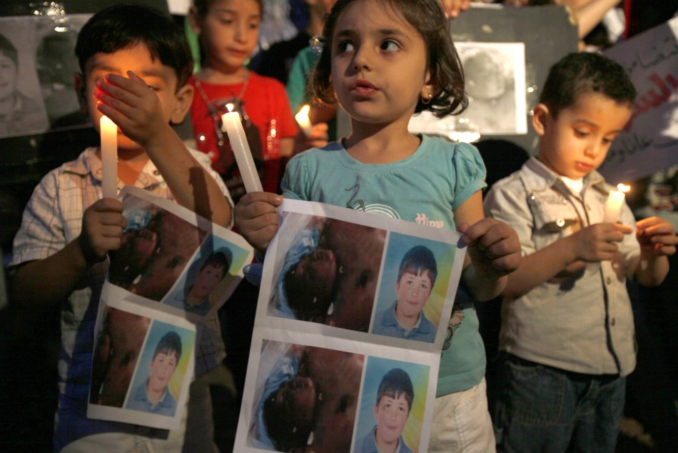Syrian children carry pictures of Syrian boy Hamza al-Khatib and hold candles during a protest in front of the United Nations building in Beirut
