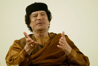 Libyan leader Gaddafi looks on during his debate on democracy with Western scholars in Sebha