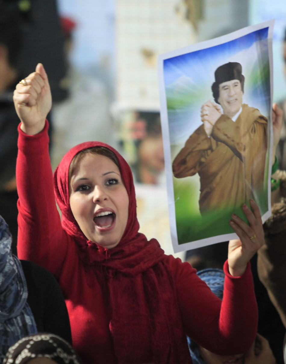 A woman holds a picture of Libyan leader Muammar Gaddafi as she chants slogans during a pro-government rally at the heavily fortified Bab al-Aziziya compound in Tripoli