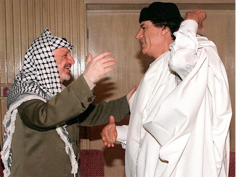 Palestinian President Yasser Arafat  reaches to embrace Libyan revolutionary leader Muammar Gaddafi