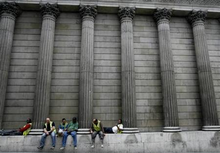 Construction workers sit amongst the columns of the Bank of England in central London