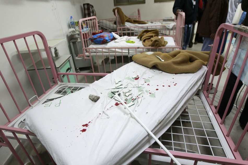 Broken glass are pictured on a blood-stained bed in Tripoli