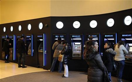 Customers use cash machines in a branch of Barclays bank in London