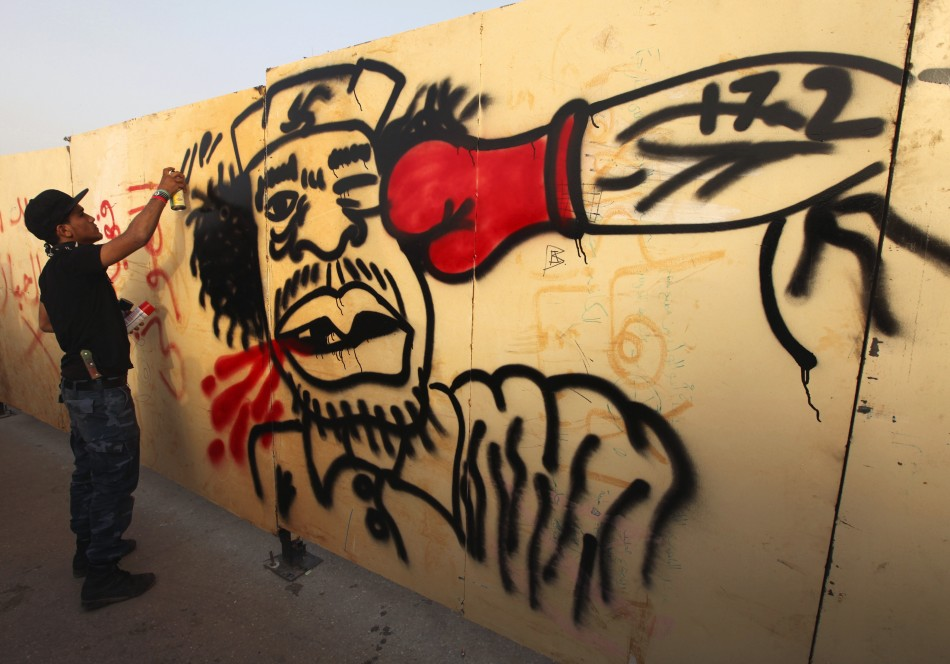 A painter paints a caricature of Libyan leader Muammar Gaddafi in Benghazi