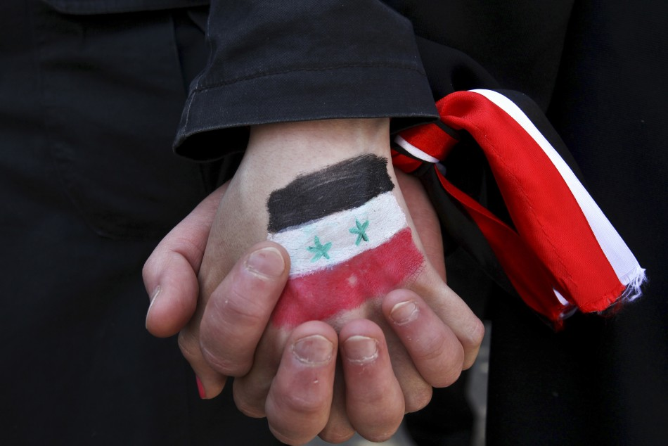 Syrians living in Jordan clasp hands during a protest against Syria's President Bashar Al-Assad outside the U.N. office in Amman