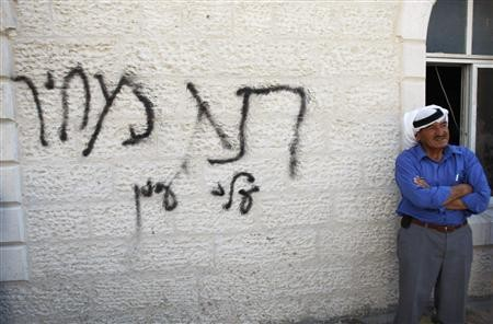 A Palestinian man stands next to Hebrew graffiti