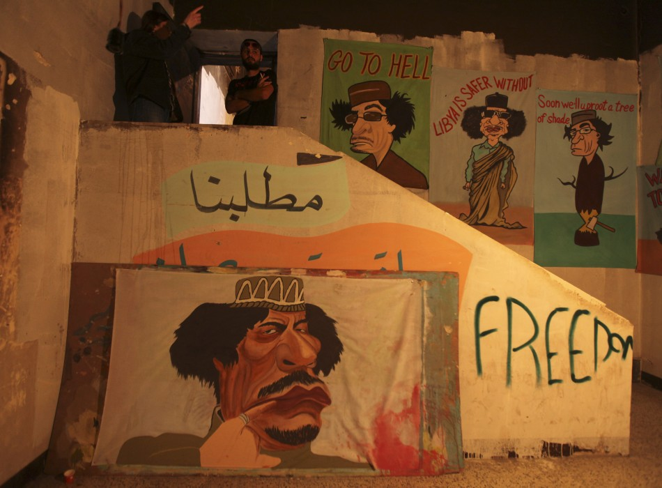 People stand next to caricatures of Muammar Gaddafi in Benghazi