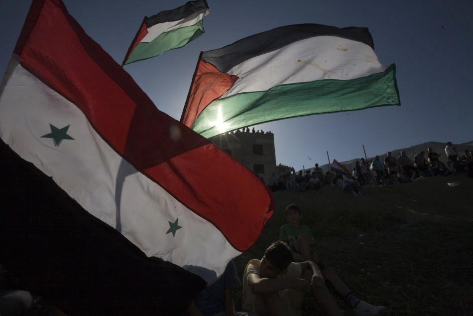 Residents of Majdal Shams hold flags on the border between Israel and Syria in the Golan Heights