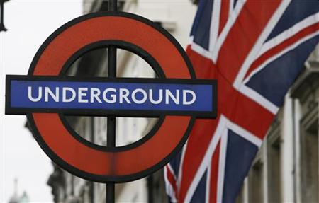 A Union Flag flies near an underground sign for Westminster tube station in London