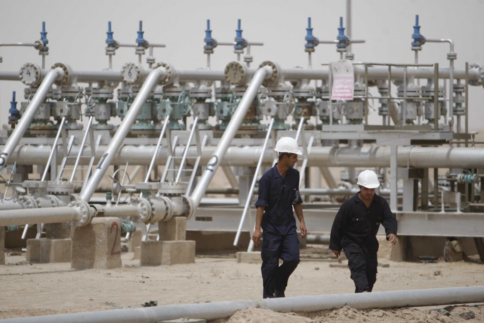 Workers walk at Rumaila oilfield in Basra, 420 km (260 miles) southeast of Baghdad