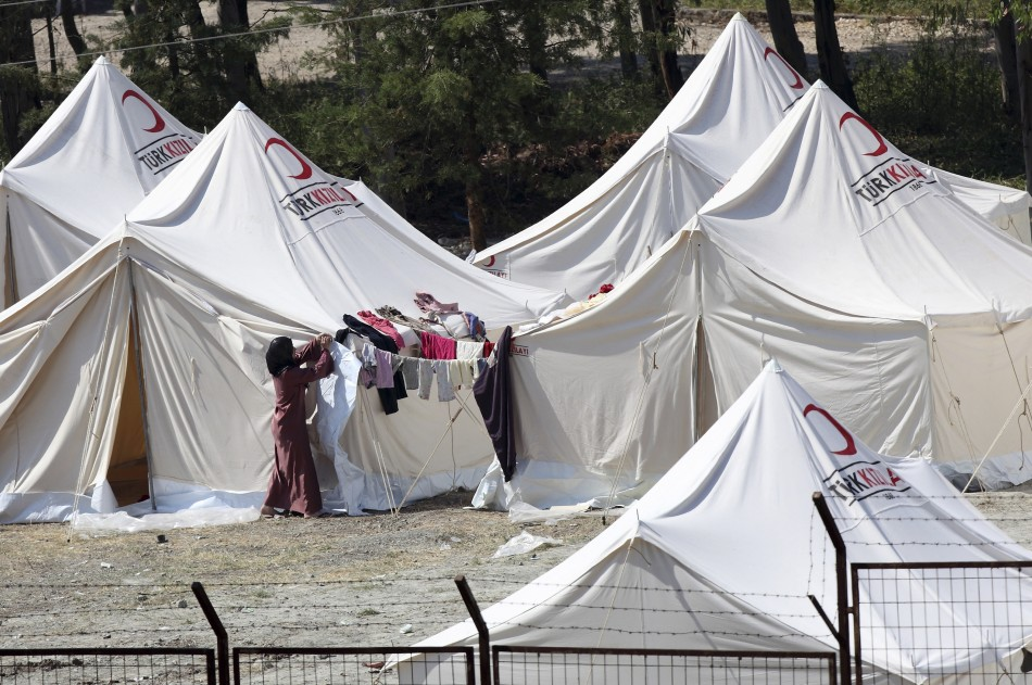 A woman rolls up a tent flap in a refugee camp in the Turkish border town of Yayladagi in Hatay province